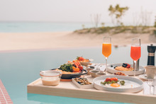 Breakfast In Swimming Pool, Floating Breakfast In Tropical Resort. Table Relaxing In Calm Pool Water, Healthy Breakfast And Fruit Plate By Resort Pool. Exotic Summer Diet. Tropical Beach Lifestyle