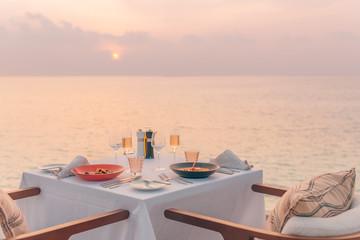 Romantyczna kolacja na plaży. Kieliszki do wina obok pięknego stołu, luksusowy hotel z widokiem na plażę