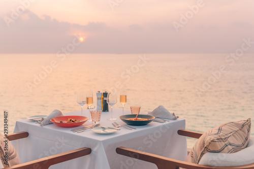 Fototapeta Romantic dinner on the beach. Wine glasses next to a beautiful dinner table setting, luxury resort hotel at beach view obraz