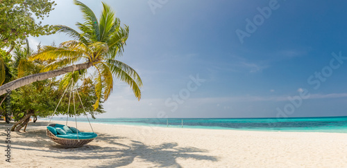 Tropical beach panorama as summer landscape with beach swing or hammock and white sand and calm sea for beach banner. Perfect beach scene vacation and summer holiday concept. Boost up color process - 293350006