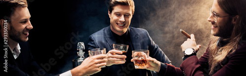 Photo panoramic shot of happy men clinking glasses with whiskey on black with smoke