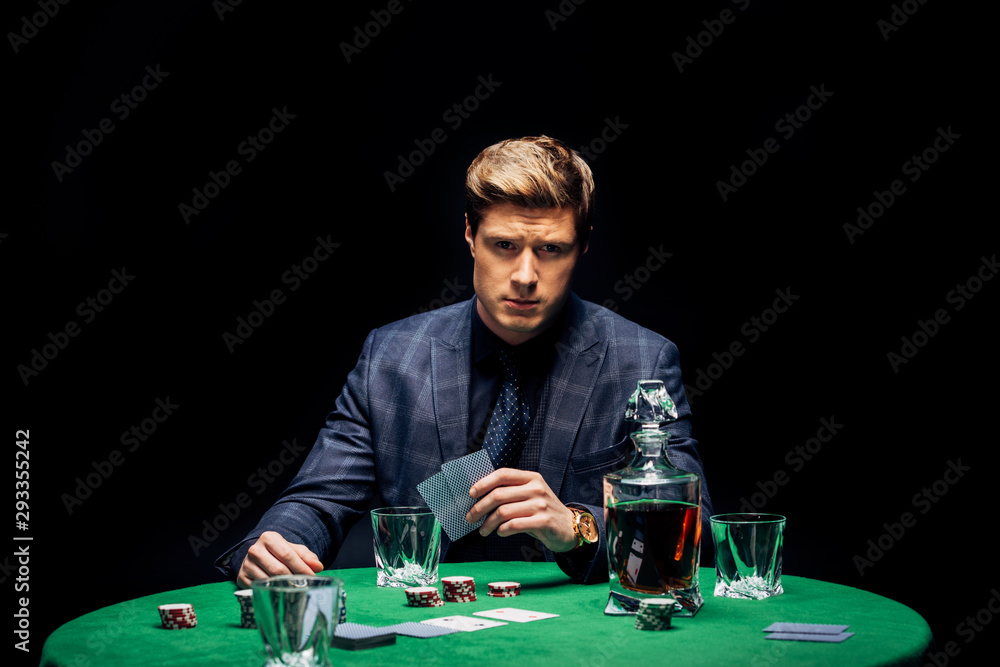 Fototapety, obrazy: selective focus of man holding playing cards isolated on black
