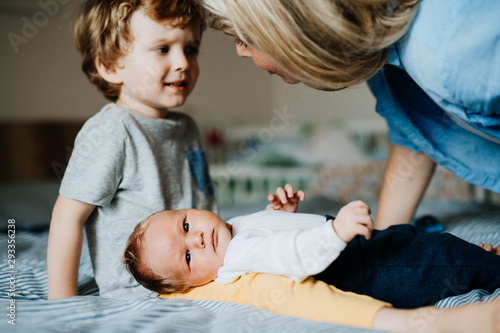 Fototapeta A beautiful young mother with a newborn baby and his brother at home. obraz