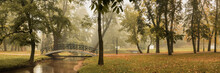 Beautiful Panoramic View Of The Autumn City Park With A Pedestrian Bridge Over A Shallow Stream With A Slight Haze From The Morning Fog In The Background
