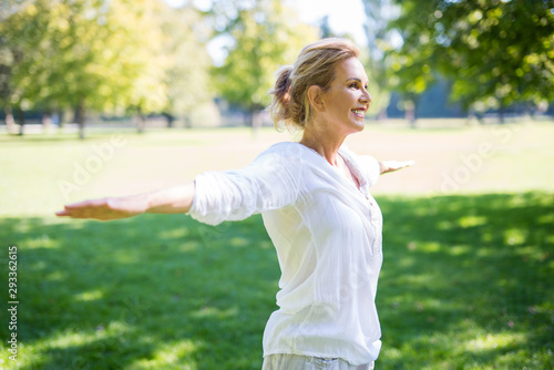Tela Attraktive ältere Frau macht Übungen im Park
