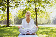 canvas print picture - Eine attraktive Best-Ager Frau macht Meditations-Übungen im Park