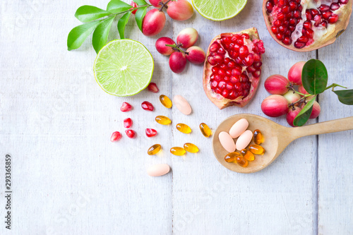 Vitamin supplements on wooden spoon with healthy fruits berry, lime, pomegranete on white wooden background.Top view.