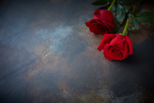 Red Roses Lie On A Textured Sp...