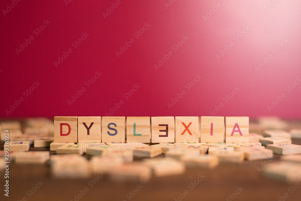Fototapeta wooden alphabet blocks with DYSLEXIA word in the center on wooden table against pink background. Concept of Dyslexia awareness and human brain development