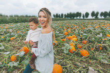 A Mother And Her Child In A Pumpkin Patch.