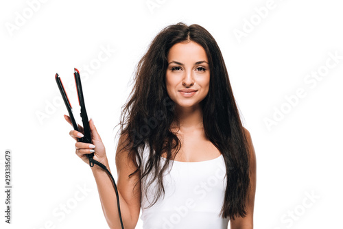 Fototapeta smiling brunette beautiful woman with straight and curly hair holding flat iron