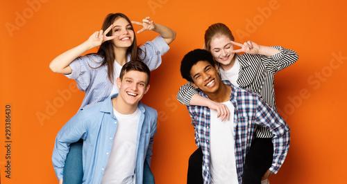 Fototapeta Excited teen guys giving piggyback ride to girls