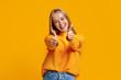 Leinwandbild Motiv Joyful teenage girl showing thumbs up on orange background
