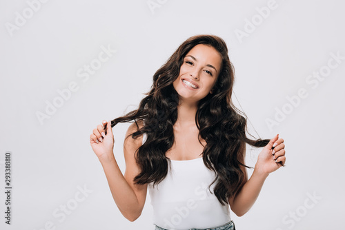 Fotografiet happy brunette beautiful woman with long curly healthy hair isolated on grey
