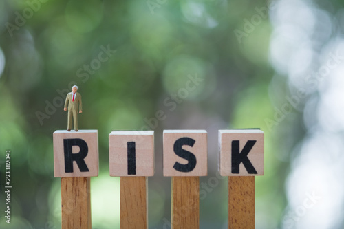 Photo Miniature people : businessman standing on a wood cube word with risk