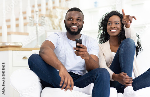 Fotografie, Tablou  Black spouses watching tv together having fun at home