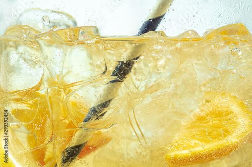 Valokuvatapetti Close up of lemon slices in stirring the lemonade and ice cubes on background