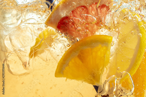 Fototapeta Close up of lemon slices in stirring the lemonade and ice cubes on background. Texture of cooling sweet summer's drink with macro bubbles on the glass wall. Fizzing or floating up to top of surface. obraz