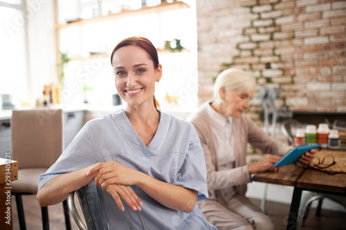 Fotografía  Beautiful hard-working caregiver wearing uniform smiling