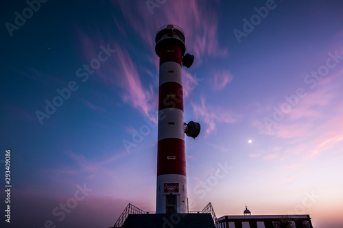 High beautiful travel concept lighthouse with blue night sky with stars and clou Canvas Print