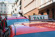 Red taxi roof sign at day. Cab on the street. Vehicles in line, parked..