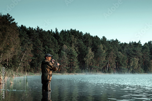 Photo A male fisherman on the lake is standing in the water and fishing for a fishing rod
