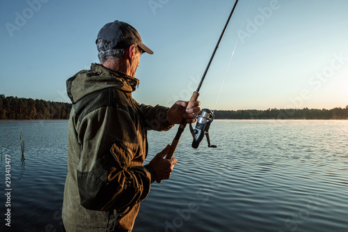 Foto auf AluDibond Fischerei Male fisherman at dawn on the lake catches a fishing rod. Fishing hobby vacation concept. Copy space.
