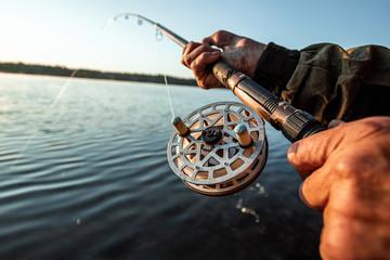 Ruke čovjeka u planu Urp drže štap, ribar lovi ribu u zoru. Koncept odmora za hobi u ribolovu. Kopiraj prostor.