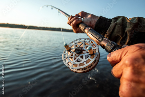 Fotografia Hands of a man in a Urp plan hold a fishing rod, a fisherman catches fish at dawn