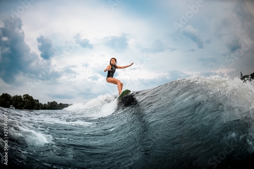 Fotografía Young girl surfs on a wakeboard in the river near forest