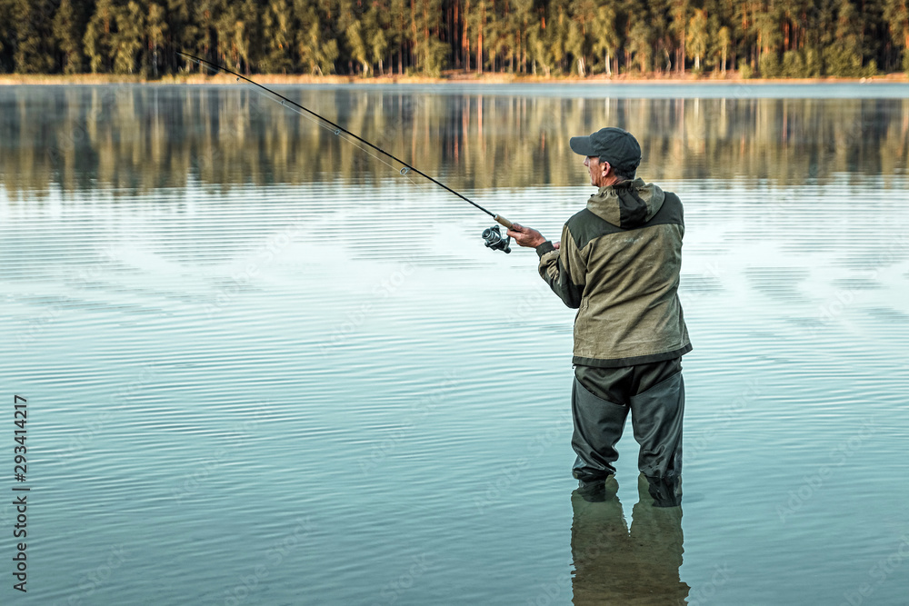 Fototapety, obrazy: A male fisherman on the lake is standing in the water and fishing for a fishing rod. Fishing hobby vacation concept. Copy space.