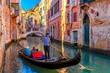 Narrow canal with gondola and bridge in Venice, Italy. Architecture and landmark of Venice. Cozy cityscape of Venice.