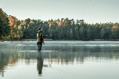 Fotografía A male fisherman on the lake is standing in the water and fishing for a fishing rod