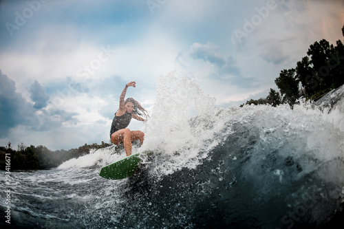 Girl wakesurfer gliding smoothly on a board