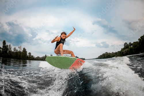 Girl wakesurfer jumping with the surf board