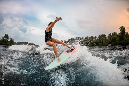 Girl wakesurfer jumping with a surf board
