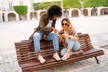 Multicultural Happy Women Talking And Using Smartphone, Sitting On Bench