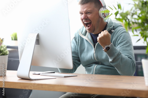 Foto Man in headphones screaming in computer monitor sitting home at table portrait