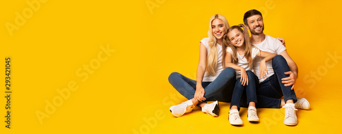 Family Embracing Sitting On Floor Over Yellow Background, Panorama Canvas-taulu