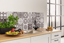 Herbs And Fruits On Kitchen Counter In Bright Kitchen Interior With Trendy Tiles On The Wall