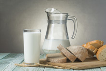 Glass Of Milk, Jug And Slices Of Fresh Bread On A Wooden Board