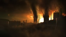 Scenic Wide Concept Animation Shot Of Heavy Industry Causing Climate Change And Pollution. Bright Golden Sunset And Dark Dystopic Black Smoke  Clouds, Silhouettes Of Chimneys And Industrial Buildings