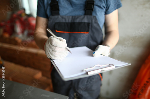 Fotomural  Focus on man hands holding pencil and write about process of unfinished room construction in order to make work easier and expertise all materials that people need