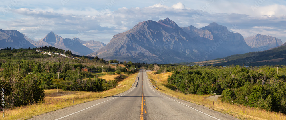 Fototapeta Beautiful View of Scenic Highway with American Rocky Mountain Landscape in the background during a Cloudy Summer Morning. Taken in St Mary, Montana, United States.