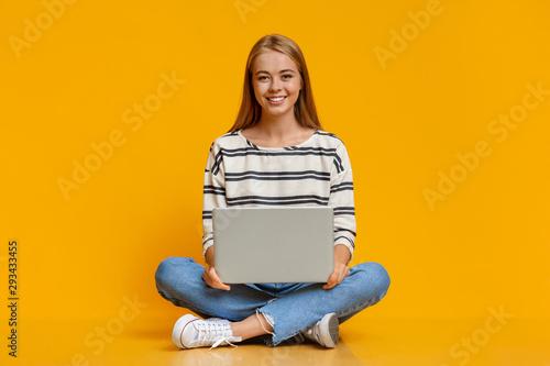 Obraz Beautiful young girl sitting with laptop on laps - fototapety do salonu
