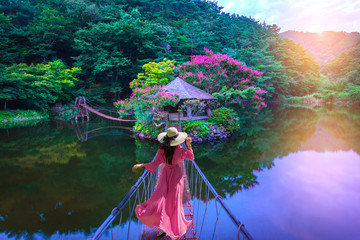 Fototapeta Orientalny Asian woman walks on a red bridge to an island resort in Suncheon, South Korea