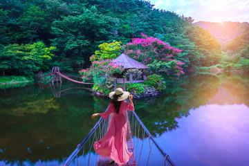 Panel Szklany Orientalny Asian woman walks on a red bridge to an island resort in Suncheon, South Korea