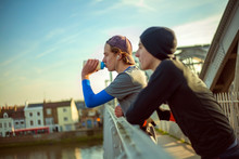 Two Young Men Drinking Water After A Run By River Thames, London, UK