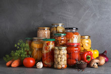 Jars Of Tasty Pickled Vegetables On Grey Table