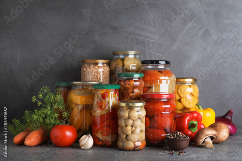 Photo Jars of tasty pickled vegetables on grey table